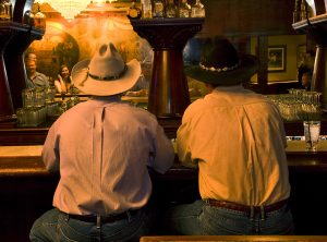 Two cowboys sitting at the hand-carved, mahogany bar in the 1889 Saloon